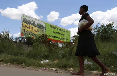 A Zimbabean woman walks past a billboard promoting male cirumcision to compate AIDS in the capital (Philimon Bulawayo/Reuters)