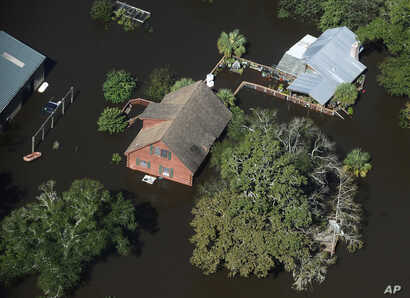 A home sits in floodwaters in Nichols, South Carolina, Oct. 10, 2016. Nearly 1 million homes and businesses still did not have power Monday morning in the Carolinas after Hurricane Matthew.