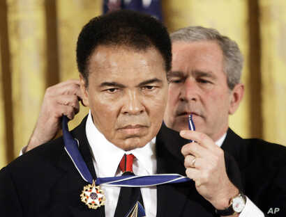 FILE - President George W. Bush presents the Presidential Medal of Freedom to boxer Muhammad Ali in the East Room of the White House, Nov. 9, 2005.