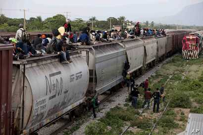 FILE - Central American migrants ride a freight train during their journey toward the U.S.-Mexico border in Ixtepec, Mexico, July 12, 2014. The migrants pay thousands of dollars per person for the illegal journey across thousands of miles in the care...