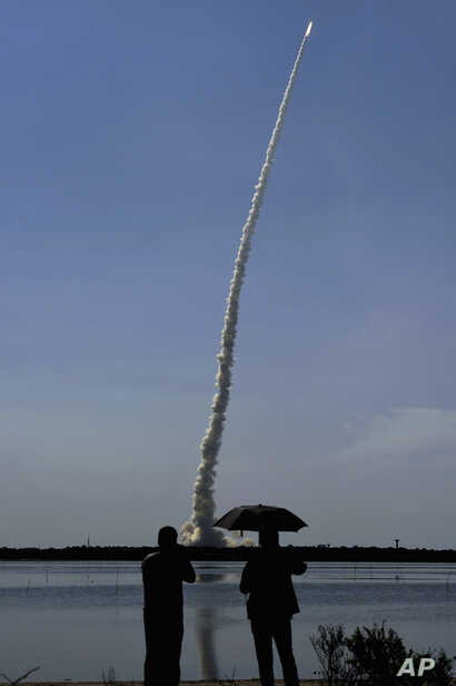 Spectators watch as India's polar satellite launch vehicle (PSLV C-34) takes off from the Satish Dhawan Space Center in Sriharikota, June 22, 2016. The rocket carries 20 satellites. (R. Senthil Kumar/Press Trust of India via AP)