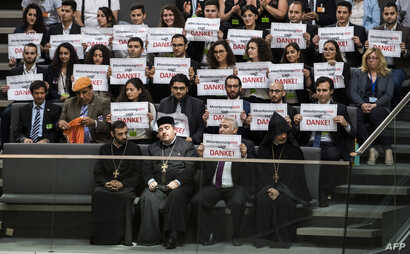 Activists and the leader of the Anerkennung Jetzt (Recognition Now) civil society initiative, Ilias Uyar (Bottom 2nd R), react after law makers voted to recognise the Armenian genocide after a debate during the 173rd sitting of the Bundestag in Berli...