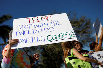 People holding placards take part in a protest in support of gun control in Coral Springs, Fla., Feb. 17, 2018.