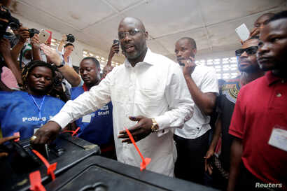 George Weah, former soccer player and presidential candidate of Congress for Democratic Change (CDC), votes at a polling station in Monrovia, Liberia