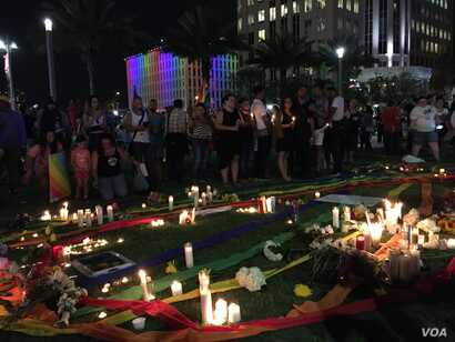 Candles and photos at a vigil for the victims and the injured of Orlando nightclub shooting. (S. Dizayee/VOA)