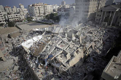 Smoke rises from the rubble of the Al-Zafer apartment tower following Israeli airstrikes Saturday that collapsed the 13-story building, in Gaza City, Sunday, Aug. 24, 2014.