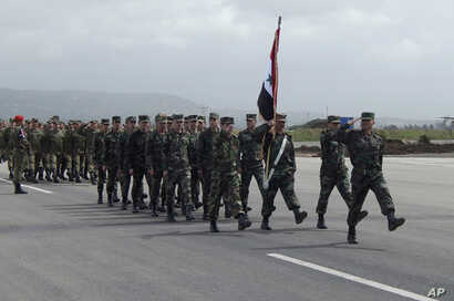 In this photo provided by the Russian Defense Ministry Press Service, Syrian troops march during a send-off ceremony for Russian troops at Hemeimeem air base in Syria, March 15, 2016.