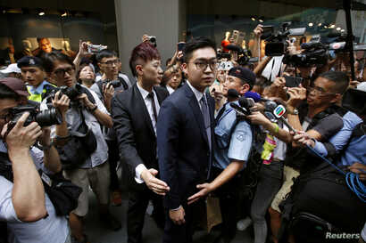 Andy Chan, a founder of the Hong Kong National Party, is surrounded by photographers as he leaves the Foreign Correspondents' Club in Hong Kong, Aug. 14, 2018.