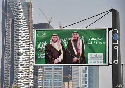 A picture taken on October 22, 2018 shows portraits of Saudi King Salman (R) and his son Crown Prince Mohammed bin Salman (MBS) in Riyadh one day before the Future Investment Initiative FII conference.