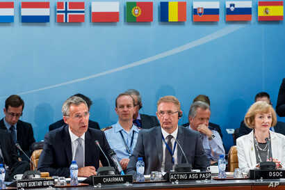 NATO Secretary General Jens Stoltenberg, left, talks during a North Atlantic Council Meeting at NATO headquarters in Brussels on Tuesday July 28, 2015.