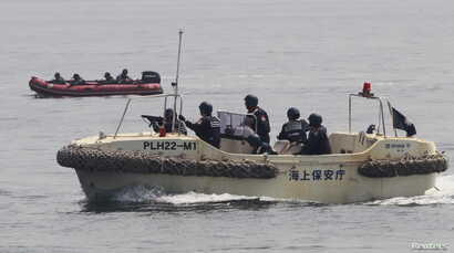 Anti-Terrorist Units of the Philippine and Japanese Coast Guards (R) prepare to target a vessel and engage the mock pirates during a combined maritime law enforcement exercise at a bay in Manila, May 6, 2015.