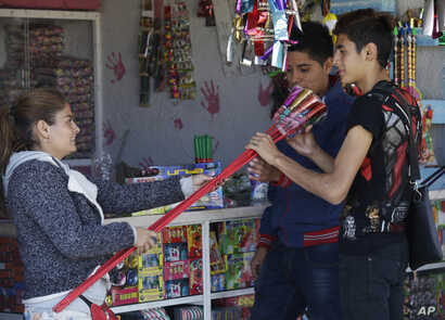 People look at fireworks for sale a the Jaltenco Market in Zumpango, Mexico, Dec. 21, 2016.  On Tuesday, a larger fireworks market in Tultepec exploded, killing and injuring dozens.