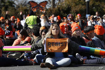 """A woman holds up a sign that says, """"resist,"""" as supporters of the Deferred Action for Childhood Arrivals (DACA) block an intersection near the U.S. Capitol  in support of DACA recipients, March 5, 2018, on Capitol Hill in Washington."""