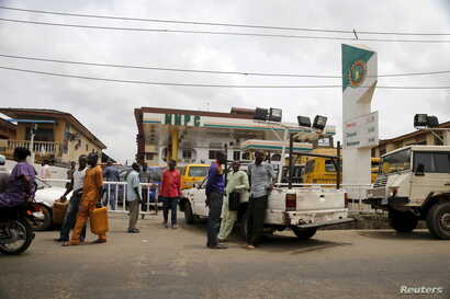 People queue with their vehicles to buy fuel at a fuel station in Agege district in Lagos, Nigeria, April 5, 2016.