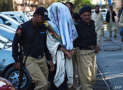 Pakistani policemen escort an arrested founding member of an ethnic Pashtun movement, Alamzeb Mehsud, with his face covered, at a court in Karachi, Jan. 22, 2019. He was arrested the day before on terrorism charges and for making anti-government spee...