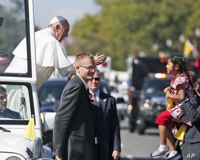 Pope Francis reaches to give a blessing to Sophie Cruz, 5, from suburban Los Angeles, during a parade in Washington, Sept. 23, 2015.