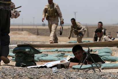 Iraqi Kurdish forces take position as they fight jihadist militants from the Islamic State of Iraq and the Levant (ISIL) in the Iraqi village of Bashir, 20 kilometers south of the city of Kirkuk, Iraq, June 29, 2014.