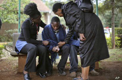 Stephen, center, who lost his father in Saturday's attack at the Westgate Mall  in Nairobi, Kenya, is comforted by relatives as he waits for the post mortem exam at the city morgue, Sept. 23, 2013.