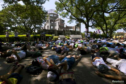 Children perform a die-in in front of the Atomic Bomb Dome in Hiroshima, western Japan, August 5, 2015. Japan will mark on Thursday the 70th anniversary of the attack on Hiroshima, where the U.S. dropped an atomic bomb on August 6, 1945, killing abou...