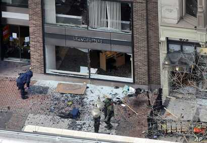 One of the blast sites on Boylston Street near the finish line of the 2013 Boston Marathon is investigated by two people in protective suits in the wake of two blasts, April 15, 2013.