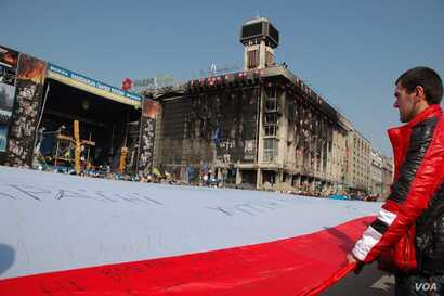 Participants at a unity rally in central Kyiv unfurl a giant flag. (Steve Herman/VOA)