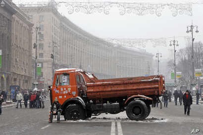 A Pro-European Union activist dressed in a military helmet sits on the side of a truck with flat tires used as a barricade on the main street Khreschatyk during a rally in Kyiv, Dec. 12, 2013.
