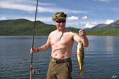 FILE - Russian President Vladimir Putin holds a fish he caught during a mini-break in the Siberian Tyva region, in this photo released by Kremlin press service on Aug. 5, 2017.