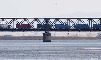 Trucks drive on the Friendship Bridge over the Yalu River which connects North Korea's Sinuiju to China's Dandong, April 11, 2013.