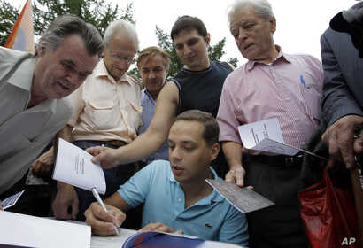 FILE - Vladimir Milov, a leader of the opposition People's Freedom Party, signs autographs during a rally of  party's supporters in Moscow, June 25, 2011.
