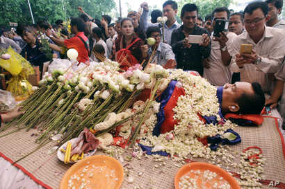 FILE - In this July 11, file photo, the body of Cambodian government critic Kem Ley is covered by the Cambodian National flag as flowers are placed during a funeral ceremony in Phnom Penh, Cambodia. Oeut Ang, the man who allegedly shot dead Kem over ...