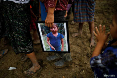 A man holds a picture of Jakelin Caal, 7, during her funeral at her home village of San Antonio Secortez, in Guatemala, Dec. 25, 2018.
