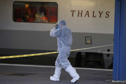 French investigating police in protective clothing prepare to enter the Thalys high-speed train where shots were fired to collect clues in Arras, France, Aug. 21, 2015.