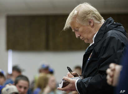 President Donald Trump signs a Bible as he greets people at Providence Baptist Church in Smiths Station, Ala., March 8, 2019, during a tour of areas where tornadoes killed 23 people in Lee County, Ala.