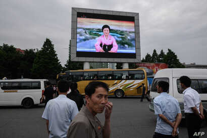 People watch a news broadcast announcing the Singapore summit meeting between North Korean leader Kim Jong Un and U.S. President Donald Trump, on a giant television screen outside the central railway station in Pyongyang, June 13, 2018.
