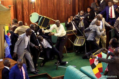 FILE - Ugandan opposition lawmakers fight with plain-clothes security personnel in the parliament while protesting a proposed age limit amendment to the constitution for the extension of the president's rule, in Kampala, Uganda, Sept. 27, 2017.