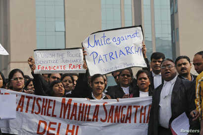 Lawyers shout slogans as they hold placards and a banner during a protest demanding the judicial system act faster against rape outside a district court in New Delhi, India, January 3, 2013.