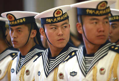 FILE - Members of a military honor guard are seen at People's Libareation Army Navy headquarters outside Beijing, China, July 15, 2014. Despite tensions over China's territorial claims over the South China Sea, Beijing and Washington continue to enga...