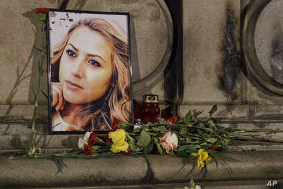 A portrait of slain television reporter Viktoria Marinova is placed on the Liberty Monument next to flowers and candles during a vigil in Ruse, Bulgaria, Oct. 9, 2018.