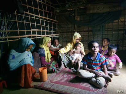 Samsun Nahar, a Rohingya widow, along with her 9 children at her bamboo-and-plastic shack in a refugee colony in Kutupalong, Cox's Bazar, Bangladesh