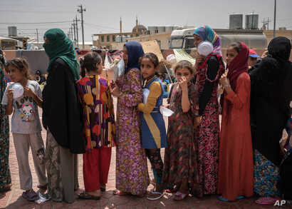 """FILE - Women and children stand in line for food at Dibaga camp for internally displaced civilians in Iraq, Aug. 7, 2016. Some say the announcement about the return of refugees is politically driven in order to make the battle for Mosul """"appear more"""