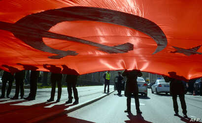 Russian military cadets hold a giant replica of the Soviet Banner of Victory as they take part in the Immortal Regiment march in Saint Petersburg, May 5, 2017.