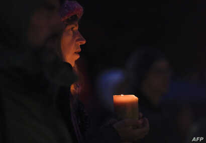 A woman holds a candle during a vigil in Squirrel Hill, Oct. 27, 2018, to remember those that died in the Tree of Life Synagogue shooting earlier in the day. The gunman who killed 11 people at a synagogue in Pittsburgh will face federal charges that ...