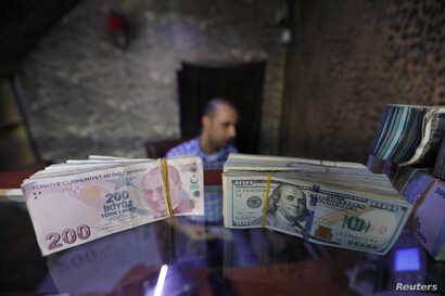 Banknotes of U.S. dollars and Turkish lira are seen in a currency exchange shop in the city of Azaz, Syria, Aug.18, 2018.