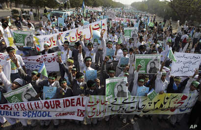 Students chant slogans while holding banners and posters showing Mumtaz Qadri, the alleged killer of Punjab governor Salman Taseer, during a rally to protest against any attempts to modify blasphemy laws, in Karachi, Pakistan, Jan. 20, 2011. Pakistan...