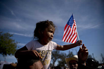 A migrant girl with a U.S. flag sits on the shoulders of a man marching with other migrants to the Chaparral border crossing in Tijuana, Mexico, Sunday, Nov. 25, 2018, as they try to reach the U.S.