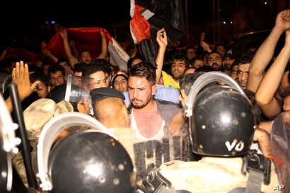 Iraqi riot police prevent protesters from storming the provincial council building during a demonstration in Basra, 340 miles (550 kilometers) southeast of Baghdad, Iraq, early Saturday, May 21, 2016.