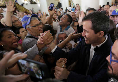 Opposition National Assembly leader Juan Guaido, right, who declared himself interim president, greets supporters as he leaves church after attending Mass in Caracas, Venezuela, Jan. 27, 2019.