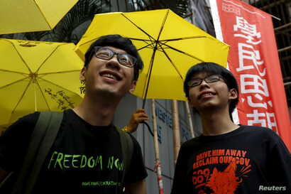 Student leaders Joshua Wong (R) and Nathan Law smile in front of supporters holding yellow umbrellas, symbol of the Occupy Central movement, outside a police station in Hong Kong, July 14, 2015.