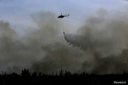 FILE - A helicopter from the Indonesian National Disaster Management agency (BNPB) drops water on a fire in Ogan Ilir, near Palembang, South Sumatra, Indonesia, Aug. 11, 2016, in this photo taken by Antara Foto.