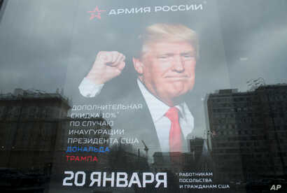 "The U.S. Embassy building is reflected in a window of a Russian military outerwear shop ""Armia Rossii"" (Russian Army) displaying a poster of U.S. President Donald Trump, in downtown Moscow, Russia, Jan. 20, 2017."